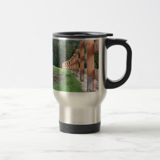 Wooden fence with forest in the background travel mug
