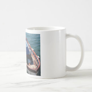 Wooden fishing boat anchored in a village port coffee mug