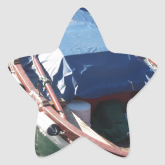 Wooden fishing boat anchored in a village port star sticker