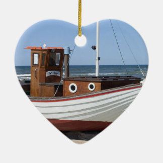 Wooden fishing boat on the beach. ceramic ornament