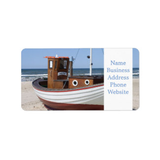 Wooden fishing boat on the beach. label