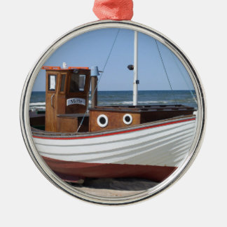 Wooden fishing boat on the beach. metal ornament