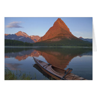 Wooden kayak in Swiftcurrent Lake at sunrise in Card