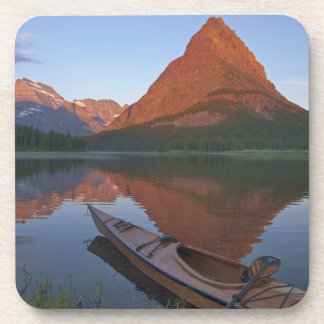 Wooden kayak in Swiftcurrent Lake at sunrise in Coaster