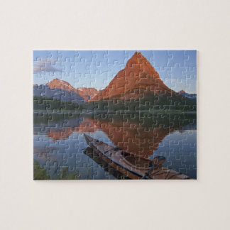 Wooden kayak in Swiftcurrent Lake at sunrise in Jigsaw Puzzle