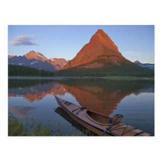 Wooden kayak in Swiftcurrent Lake at sunrise in Postcard