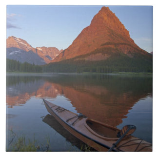 Wooden kayak in Swiftcurrent Lake at sunrise in Tile