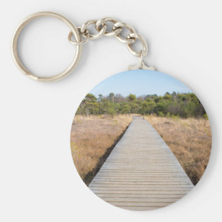 Wooden path in grass and forest winters landscape. keychain