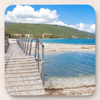 Wooden pedestrian bridge on greek beach coaster