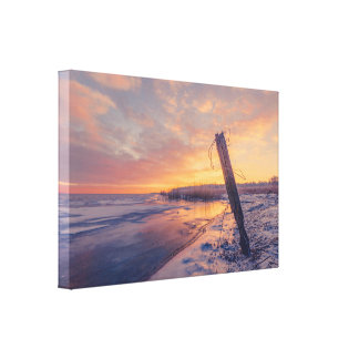 Wooden post with barb wire in the sunrise canvas print