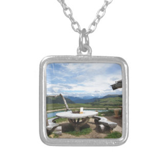 Wooden table next to hut cabin in mountain alps silver plated necklace
