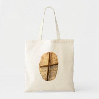 Wooden thin cross on white brick church wall bag