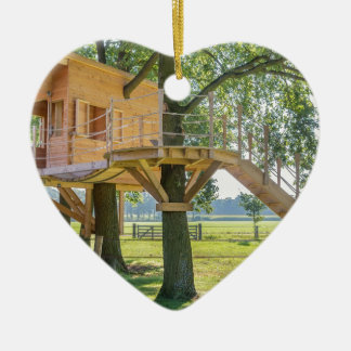 Wooden tree house in oak tree with grass ceramic ornament