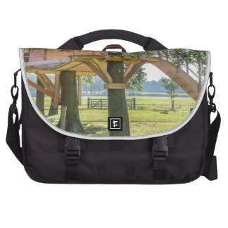 Wooden tree house in oak tree with grass commuter bag