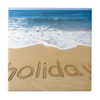 Word holiday written in sand on beach tile