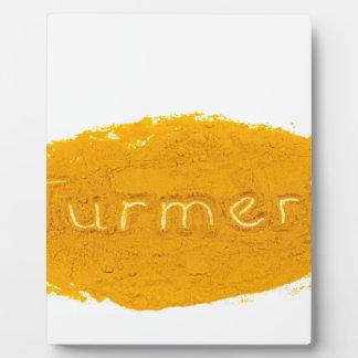 Word Turmeric written in powder on white backgroun Plaque