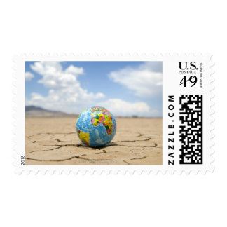World globe on dry, cracked,  lake bed in stamp