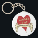 "World&#39;s Best Teacher&#39;s Assistant Keychain<br><div class=""desc"">Red heart with a golden ribbon to honor a world&#39;s best teacher&#39;s assistant</div>"