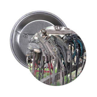 Worn leather horse bridles hanging on wooden fence button