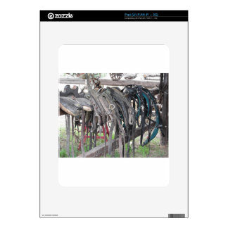 Worn leather horse bridles hanging on wooden fence iPad skin
