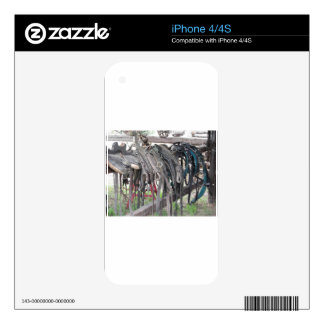 Worn leather horse bridles hanging on wooden fence iPhone 4 skins