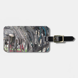 Worn leather horse bridles hanging on wooden fence luggage tag