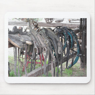 Worn leather horse bridles hanging on wooden fence mouse pad