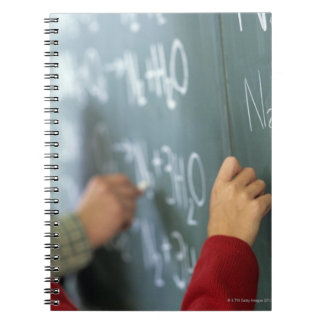 writing chemical equations on the blackboard in spiral note books