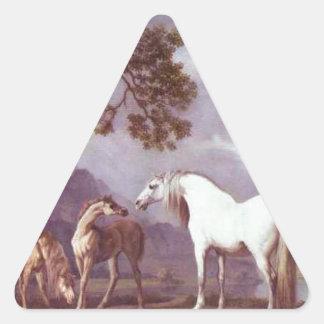 Yeguas y potros en un paisaje montañoso pegatina triangular