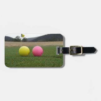 yellow and pink golf balls, bag tag