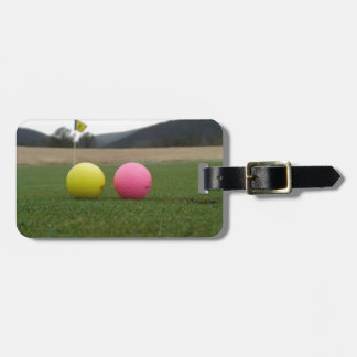 yellow and pink golf balls, luggage tags