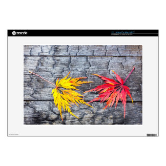 Yellow and red maple leaf on black burnt wood laptop skins