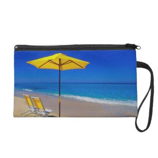 Yellow beach umbrella and chairs on pristine wristlet purses