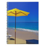 Yellow beach umbrella and chairs on pristine spiral notebook