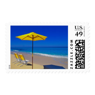 Yellow beach umbrella and chairs on pristine postage