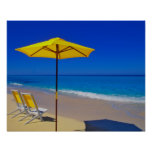 Yellow beach umbrella and chairs on pristine print