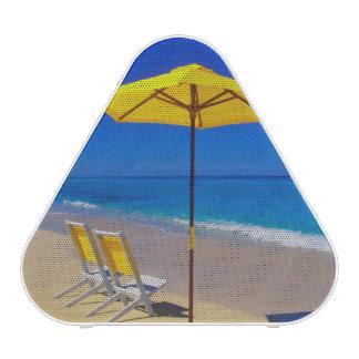 Yellow beach umbrella and chairs on pristine speaker