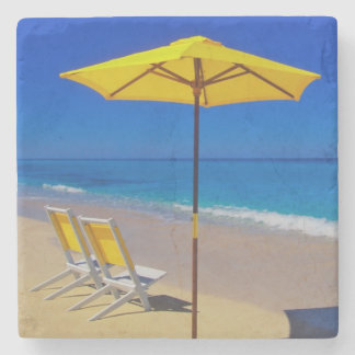 Yellow beach umbrella and chairs on pristine stone coaster