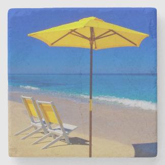 Yellow beach umbrella and chairs on pristine stone coaster