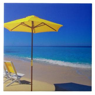 Yellow beach umbrella and chairs on pristine ceramic tiles