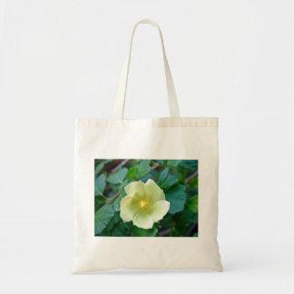 Yellow flower against dark green leaves tote bags