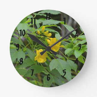 yellow flowers against green leaves round wall clocks