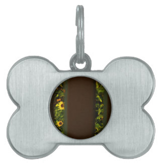 Yellow flowers through wide brown fence pet name tags