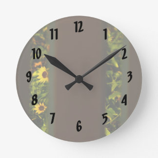 Yellow flowers through wide brown fence round clock