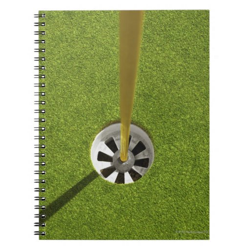 Yellow golf flag pole and hole notebooks