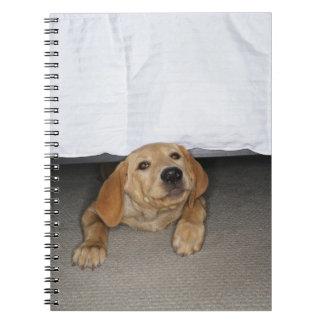 Yellow lab puppy stuck under bed spiral notebook