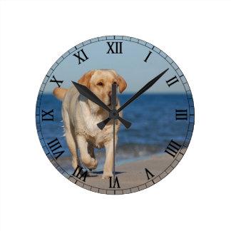 Yellow labrador retriever on the beach round wall clocks