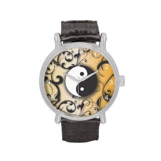 Yin negro y Yang en el fondo de bronce Reloj