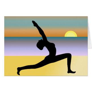 Yoga en la mujer de la playa que presenta tarjetas