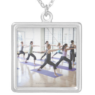 Yoga instructor teaching a class of women the silver plated necklace